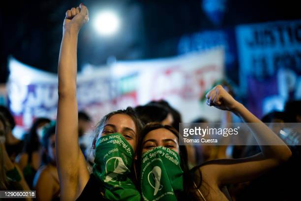 Pro-choice activist pose for a photo while raising their fists outside the National Congress as Deputies vote on a bill to legalize abortion on...