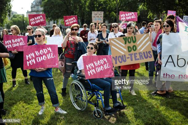 Pro-choice campaigners hold placards outside the Houses of Parliament during a demonstration to urge the Government to extend the same laws on...