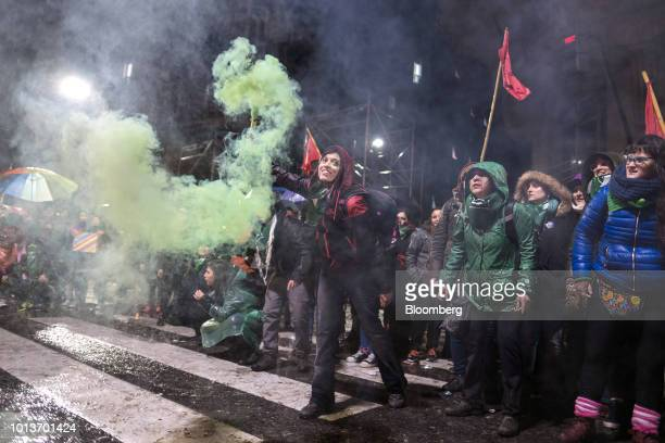 A prochoice demonstrator holds a green smoke flare during a protest in Buenos Aires Argentina early on Thursday Aug 9 2018 After months of heated...