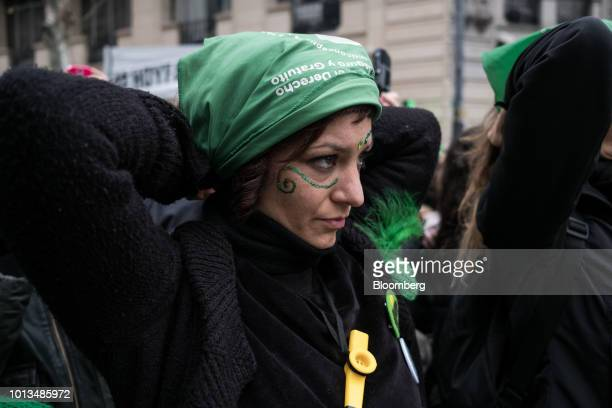 A prochoice demonstrator places a green handkerchief on her head during a protest outside of the National Congress building in Buenos Aires Argentina...
