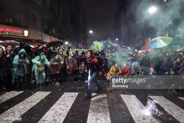 A prochoice demonstrator runs with a green smoke flare during a protest in Buenos Aires Argentina early on Thursday Aug 9 2018 After months of heated...