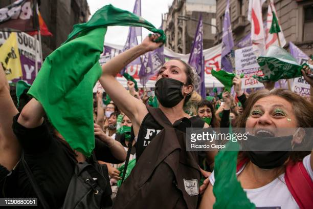Pro-choice demonstrators hold up green kerchiefs and shout slogans as Deputies give half sanction to a bill to legalize abortion on December 11, 2020...