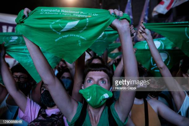Pro-choice demonstrators hold up their green bandanas as they watch the lower house representatives session on a giant screen placed outside the...