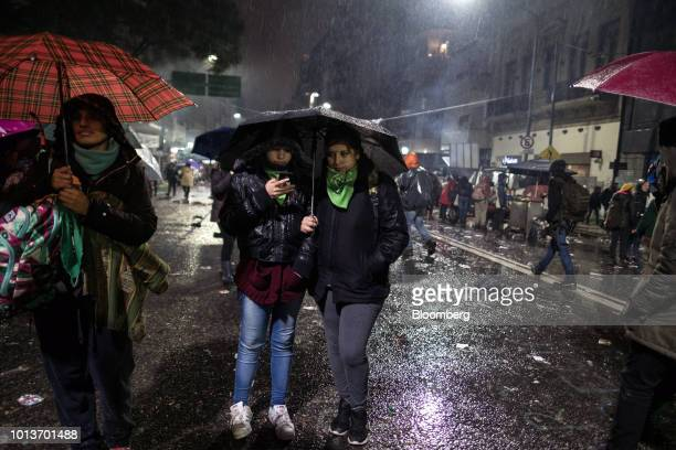Prochoice demonstrators stand under umbrellas during a protest in Buenos Aires Argentina early on Thursday Aug 9 2018 After months of heated debate...