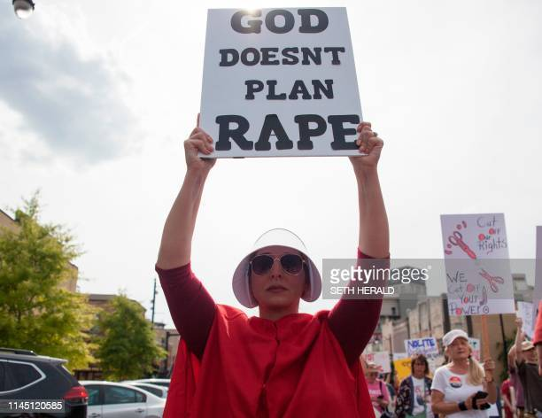 ProChoice protester dressed as a character from the dystopian drama web television series Handmaid's Tale holds a sign reading God doesn't plan rape...