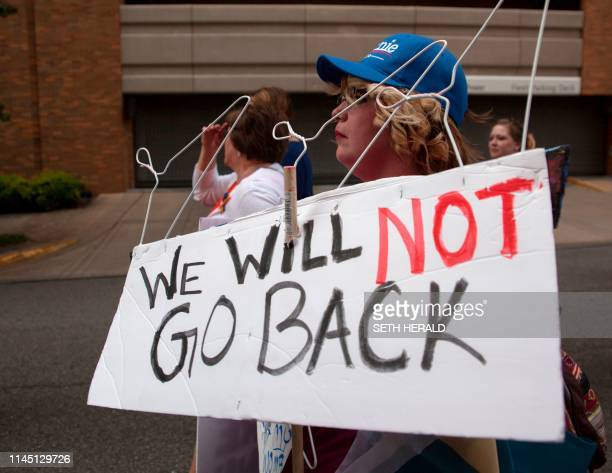 ProChoice protesters with metal hangers on a sign march through the streets of Birmingham Alabama during the March For Reproductive Freedom on May 19...