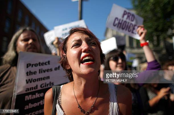 A ProChoice supporter holds placards in front of the gates of the Irish Parliament building in Dublin on July 10 2013 ahead of a vote to introduce...