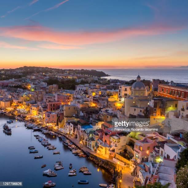 procida, multi colours houses in la corricella harbour at sunset. naples, campania, italy. capital of culture 2022 - baia foto e immagini stock