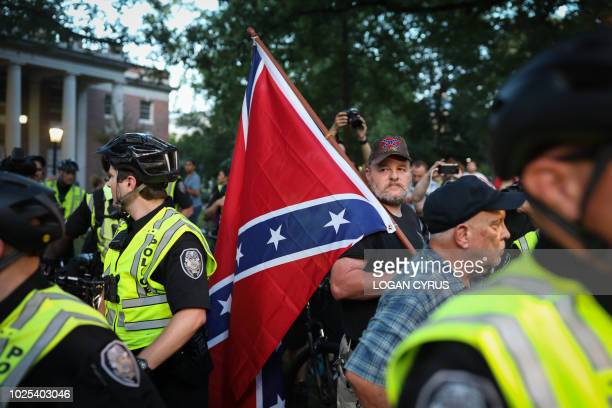 """Pro-confederacy protestors receive a police escort through a shouting crowd to where the """"Silent Sam"""" statue once stood before it's toppling last..."""