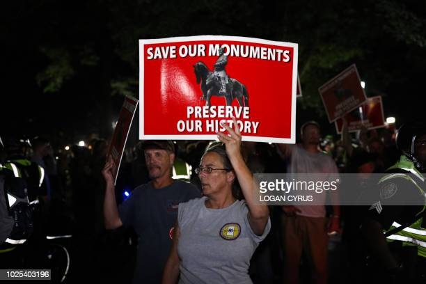 """Pro-confederacy protestors receive a police escort through a shouting crowd to their vehicles after protesting where the """"Silent Sam"""" statue once..."""