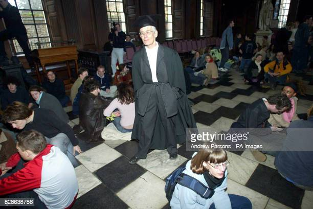 A procter walks though the middle of the protest as Cambridge University students recalled protests of the past by staging a sitin in opposition to...