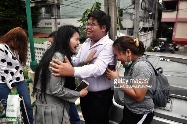 TOPSHOT Prodemocracy activist Bunkueanun Francis Paothong comforts loved ones before he enters the Dusit Police Station to answer charges of harming...