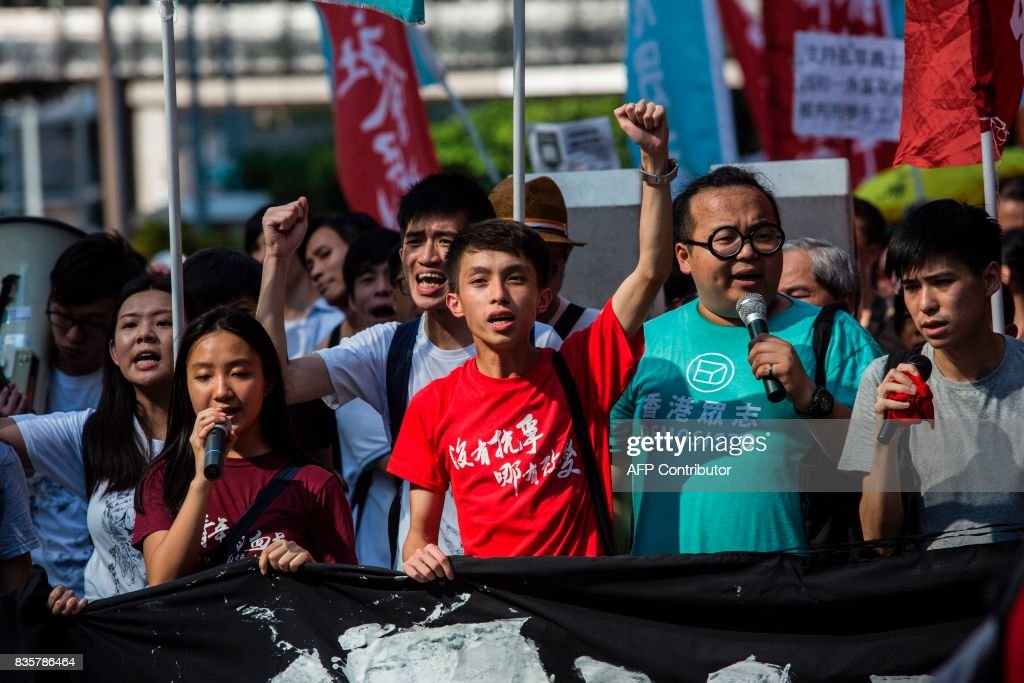 Pro-democracy activist Figo Chan (C) and Derek Lam (2nd R) march in Hong Kong on August 20, 2017, to protest the jailing of Joshua Wong, Nathan Law and Alex Chow (not pictured), the leaders of Hong Kong's 'Umbrella Movement', after their sentencing at the High Court on August 17. Wong, Law and Chow were handed sentences of six to eight months by the Court of Appeal for their role in 2014's massive Umbrella Movement protests, which called for fully free leadership elections and were an unprecedented challenge to Beijing. /