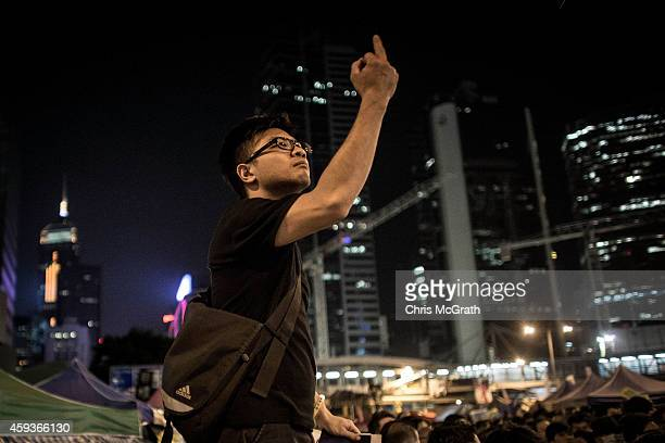 A prodemocracy activist gestures towards the main stage while listening to speeches during a rally on the streets outside Hong Kong's Central...