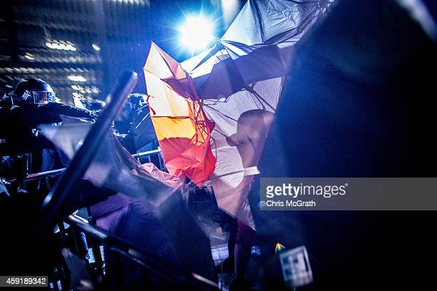 A prodemocracy activist is silhouetted behind an umrella as they clash with police outside the Legislative Council building on November 19 2014 in...