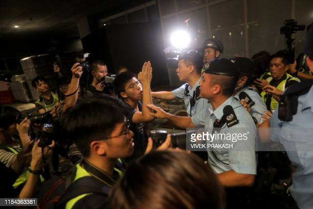 Pro-democracy activist Joshua Wong confronts police after taking part in a march to the West Kowloon rail terminus against the proposed extradition...