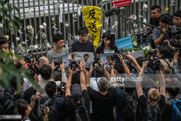 Pro-democracy activist Joshua Wong holds a protest poster as he speaks to members of the media outside the Legislative Council building following a...