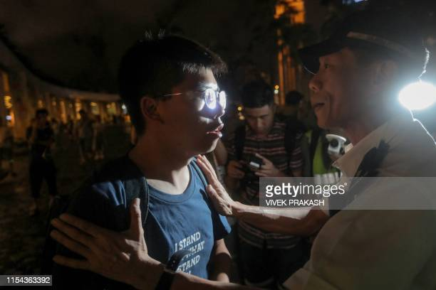 Pro-democracy activist Joshua Wong is hold by a policeman as he confronts police after taking part in a march to the West Kowloon rail terminus...