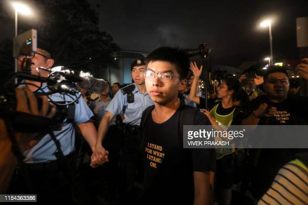 Pro-democracy activist Joshua Wong looks on as he confronts police after taking part in a march to the West Kowloon rail terminus against the...