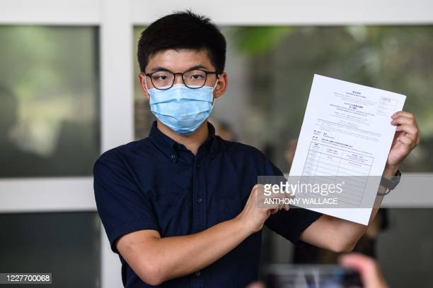 Pro-democracy activist Joshua Wong poses for the press while holding a candidate nomination form as he announces his intention to run for the...