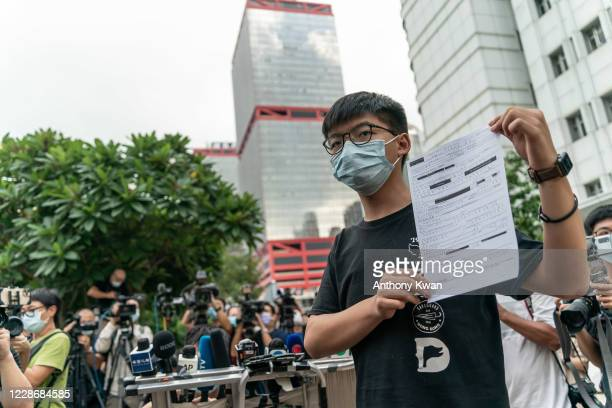 Pro-democracy activist Joshua Wong speaks to members of media as he holds a bail document after leaving Central police station on September 24, 2020...