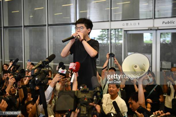 Prodemocracy activist Joshua Wong speaks to the media and supporters outside the Legislative Council shortly after being released from prison on June...