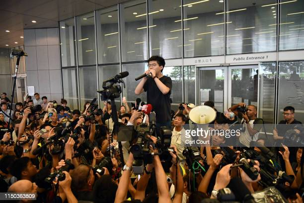 Pro-democracy activist Joshua Wong speaks to the media and supporters outside the Legislative Council shortly after being released from prison on...