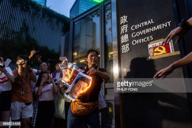 Pro-democracy activist Lui Yuk-lin burns a portrait of Chinese President Xi Jinping outside the Central Government Offices after attending a protest...