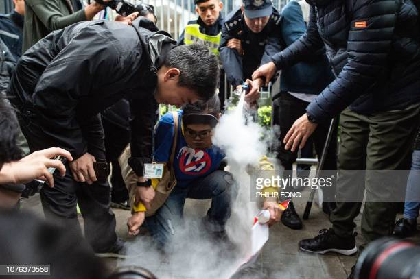 Prodemocracy activist Lui Yuklin wearing a mask of Andy Chan convenor of the Hong Kong National Party tries to burn a placard in front of the...