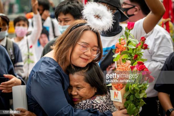 """Pro-democracy activist Panusaya """"Rung"""" Sithijirawattanakul hugs a supporter as she arrives at the Office of the Attorney General to be indicted on..."""
