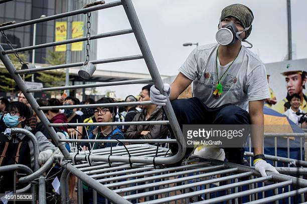 Pro-democracy activist sits on a barricade on the road outside Citic Tower on November 18, 2014 in Hong Kong, Hong Kong. Baliffs oversaw the removal...