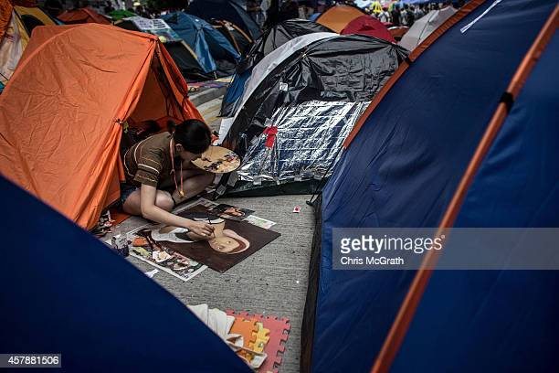 A prodemocracy activist works on a painting amongst tents on a street outside Hong Kong's Government Complex in on October 26 2014 in Admiralty...