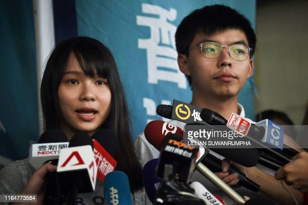 Pro-democracy activists Agnes Chow and Joshua Wong speak to the press after they were released on bail at the Eastern Magistrates Courts in Hong Kong...
