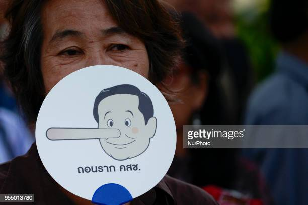 Pro-democracy activists displays a placard with a cartoon depicting Thai Prime Minister Prayut Chan-O-Cha during a demonstration against military's...