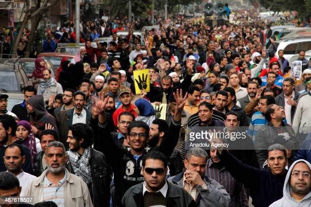 Pro-democracy activists flash Rabia sign as they march during the Friday protests against the military coup in the Ain Shams district of Cairo,...