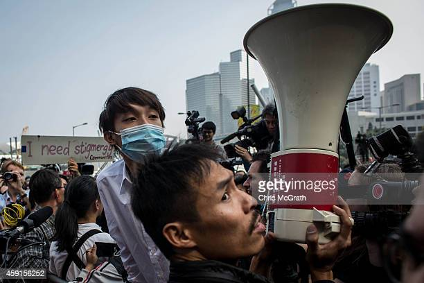 Pro-democracy activists gather around barricades and give instructions over a megaphone to fellow protesters on the road outside Citic Tower on...