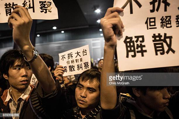 Pro-democracy activists hold signs in opposition to a speech being given on the main stage during a rally on the streets outside Hong Kong's Central...