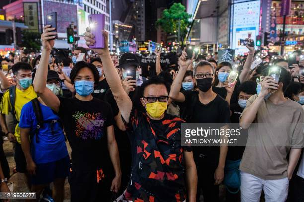 TOPSHOT Prodemocracy activists hold up their mobile phone torches as they sing during a rally in the Causeway Bay district of Hong Kong on June 12...