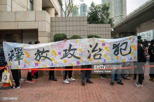 """Pro-democracy activists line up outside the West Kowloon court as they hold a banner reads """"Release all political prisoners on March 1, 2021 in Hong..."""