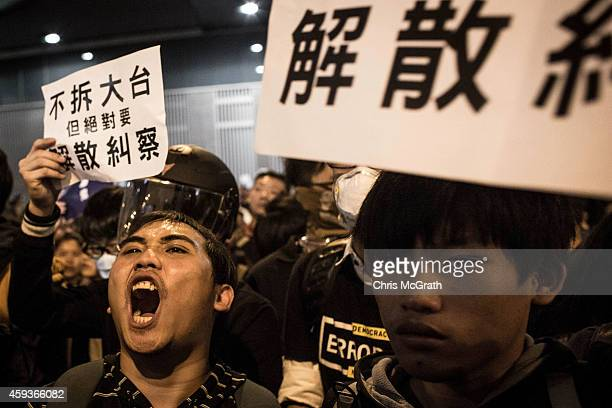 Pro-democracy activists yell and hold signs in opposition to a speech being given on the main stage during a rally on the streets outside Hong Kong's...
