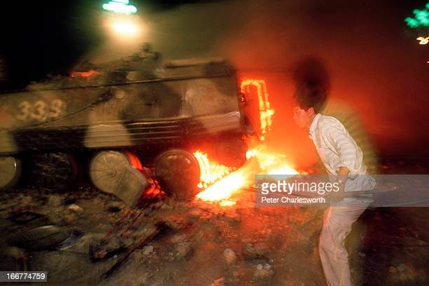 A prodemocracy demonstrator attacks a burning armoured personnel carrier during the fighting that raged on Changan Avenue as soldiers marched and...