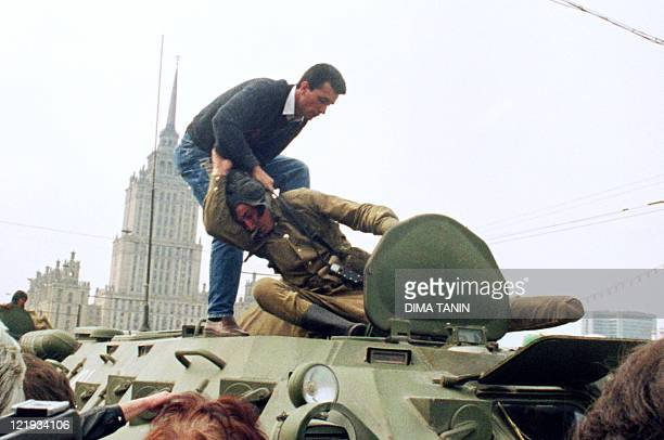Pro-democracy demonstrator fights with a Soviet soldier on top of a tank parked in front of the Russian Federation building 19 August 1991 after a...
