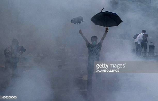 A prodemocracy demonstrator gestures after police fired tear gas towards protesters near the Hong Kong government headquarters on September 28 2014...
