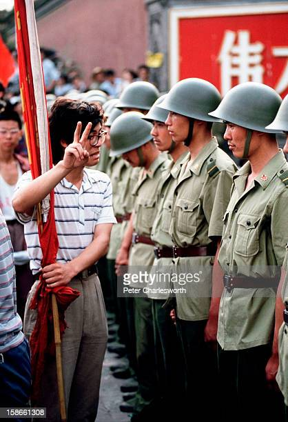 Pro-democracy demonstrator gives the V for Victory sign to soldiers who are lined up, standing guard outside the Chinese Communist Party's...