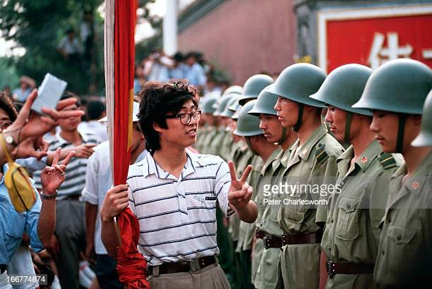 A prodemocracy demonstrator gives the V for Victory sign to soldiers who are lined up standing guard outside the Chinese Communist Party's...