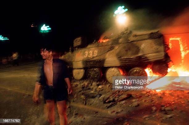 Pro-democracy demonstrator passes a burning armoured personnel carrier during the fighting that raged on Changan Avenue as soldiers marched and shot...