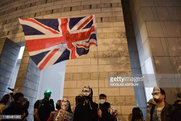 A prodemocracy demonstrator seen wearing a mask depicting former British consulate worker Simon Cheng waves the Union Jack flag as he and others...