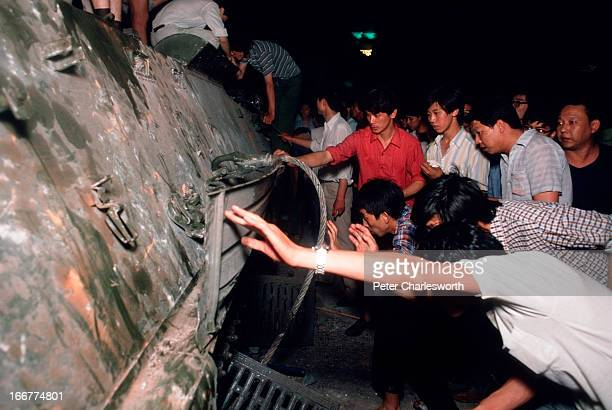 Prodemocracy demonstrators inspect an armoured personnel carrier that has been destroyed during the fighting that raged on Changan Avenue as soldiers...