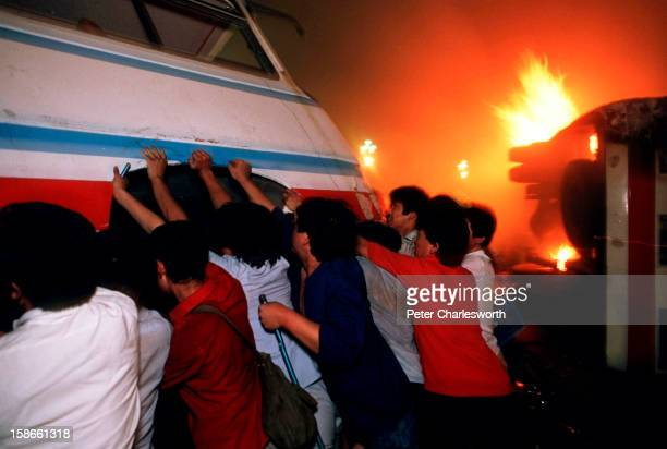 Pro-democracy demonstrators overturn a bus in front of a burning truck on Changan Avenue in order to try and hold up soldiers who are fighting their...