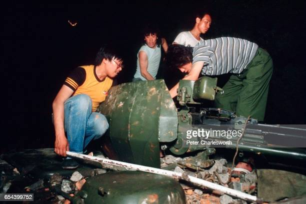 Prodemocracy demonstrators try to break the gun on top of an armoured personnel carrier that has been destroyed during the fighting that raged on...